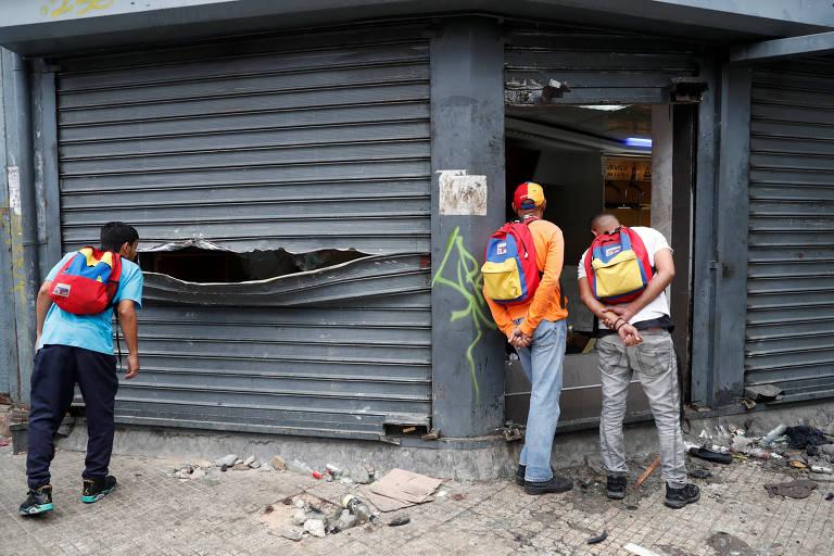 Venezuelanos observam estragos em loja de Caracas nesta quinta-feira (24) após protesto do dia anterior