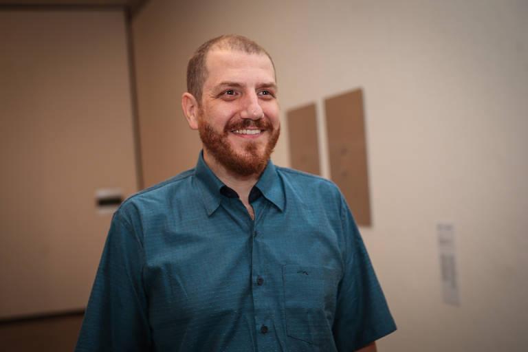 homem ruivo com cabelo curtinho e barba sorri