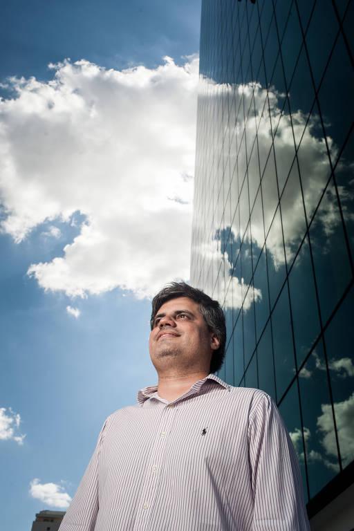Homem de camisa clara; céu azul com uma nuvem ao fundo