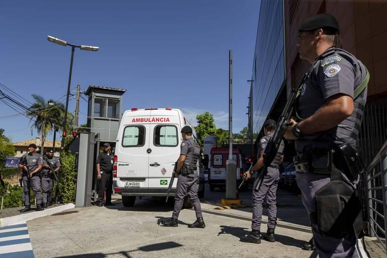 Policiais acompanham comitiva presidencial na chegada ao Hospital Albert Einstein para internação do presidente Jair Bolsonaro; ao fundo ambulância