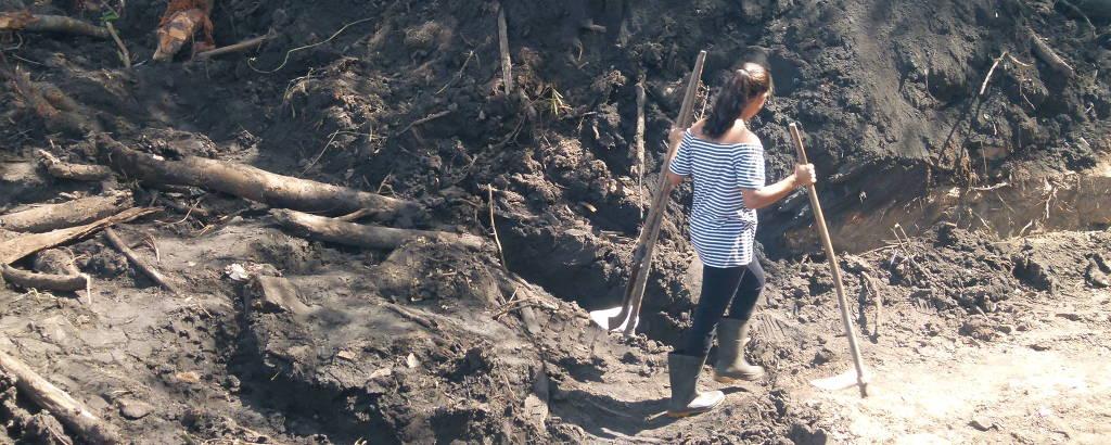 Sônia Monteiro em área coberta pela lama; ela escava por conta própria área em que estaria cunhado