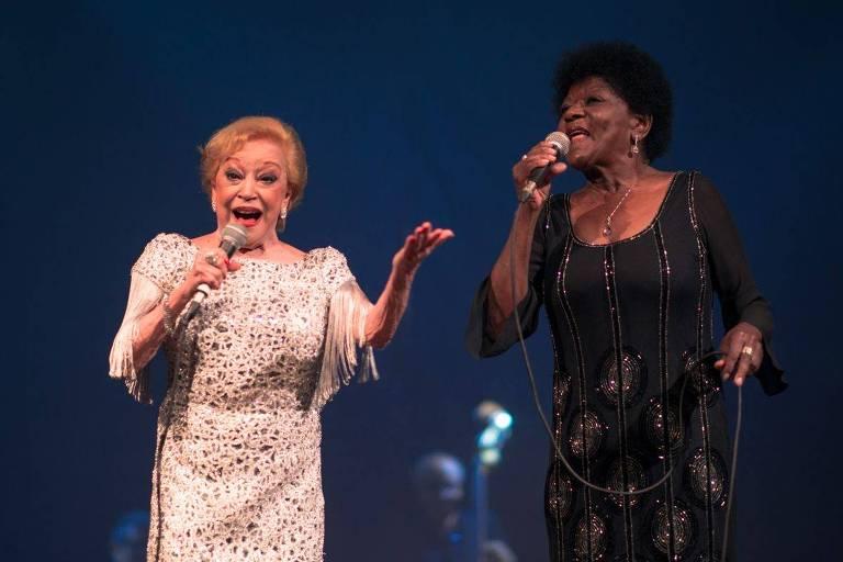 Claudette Soares e Alaíde Costa cantam em apresentação ao vivo. Claudette está à esquerda, de vestido branco e segurando o microfone. Alaíde está à direita, de vestido preto e também segurando microfone