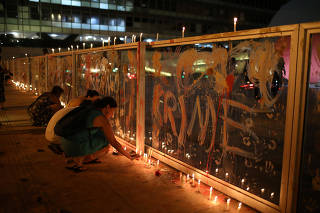 People light candles during a vigil in front of the Brazilian mining company Vale SA headquarters in Rio de Janeiro