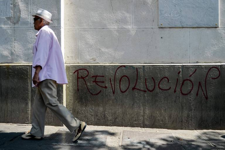 """Homem passa ao lado de grafite em que está escrito """"Revolução"""" em rua de Caracas"""