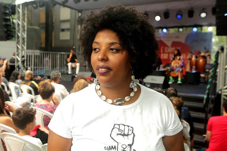 mulher negra usa camisa branca com jovens sentados ao fundo. ela olha para o lado
