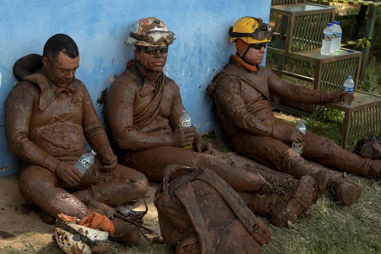 Membros das forças de resgate descansam após trabalhos de busca na lama