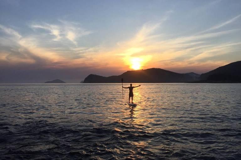 Homem em prancha no mar, com braços abertos, e pôr do sol ao fundo