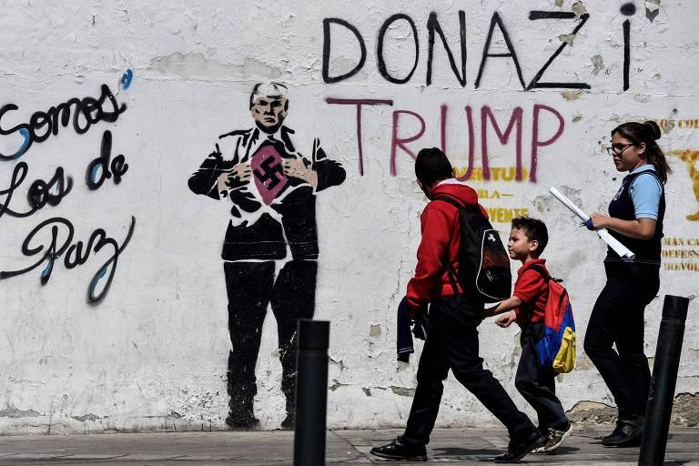 Moradores de Caracas passam por mural com desenho de Donald Trump com símbolo nazista