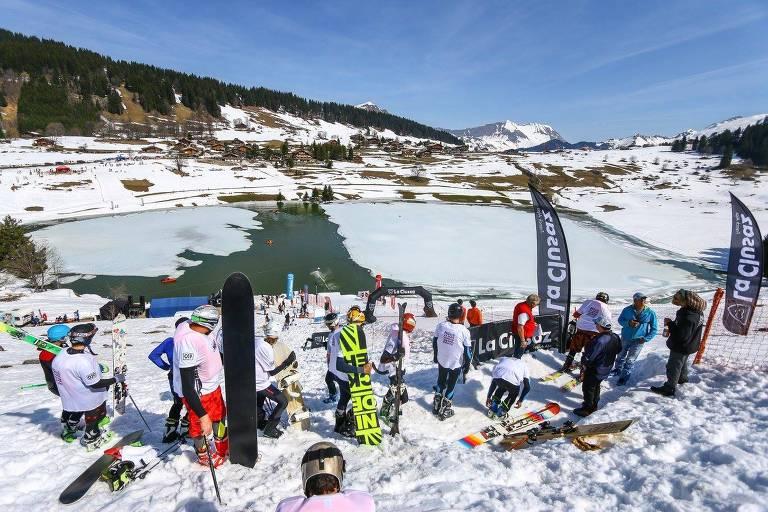 Pessoas com esquis ao lado de lago congelado, em montanha coberta de neve