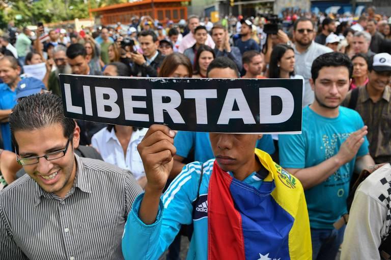 Venezuelano segura placa com a palavra 'liberdade' em ato contra Maduro nesta quarta (30) em Caracas