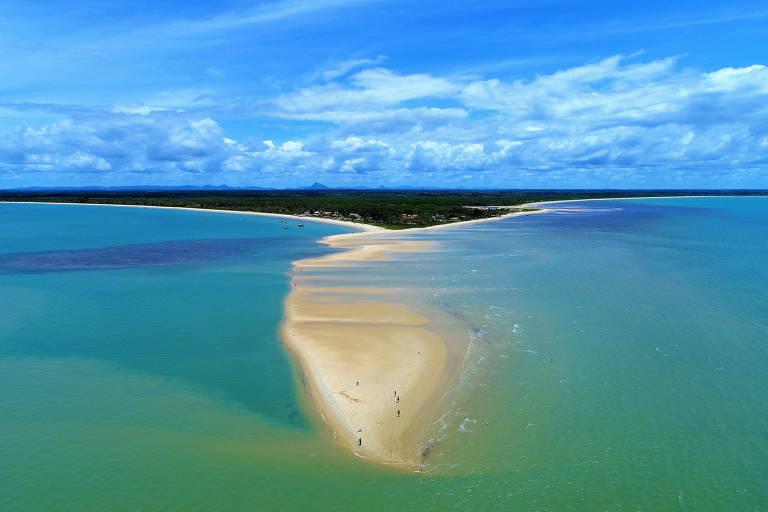 Ponta de areira que invade o mar, com águas verdes e cristalinas