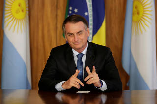 FILE PHOTO: Brazil's President Jair Bolsonaro gestures during a meeting with Argentina's President Mauricio Macri, at the Planalto Palace in Brasilia
