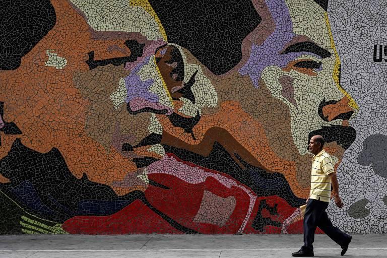 Homem passa por mosaico representando Hugo Chávez e o ditador Nicolás Maduro em Caracas