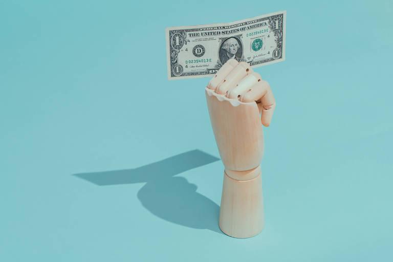 Mão de boneco segurando cédula de dólar