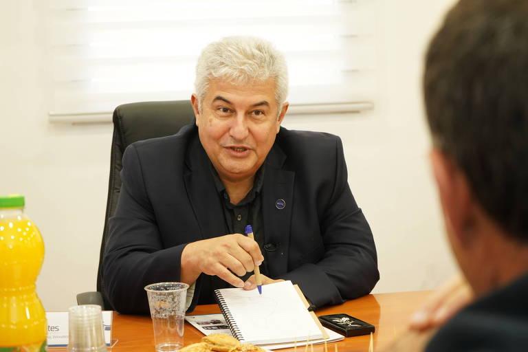 Marcos Pontes, ministro da Ciência e Tecnologia, sentado, com folha de papel e caneta nas mãos