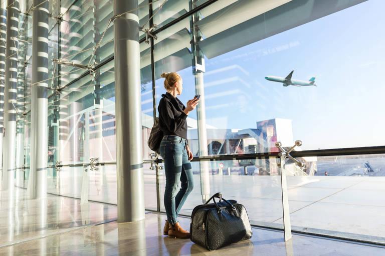 Mulher com celular na mão olha para avião em aeroporto