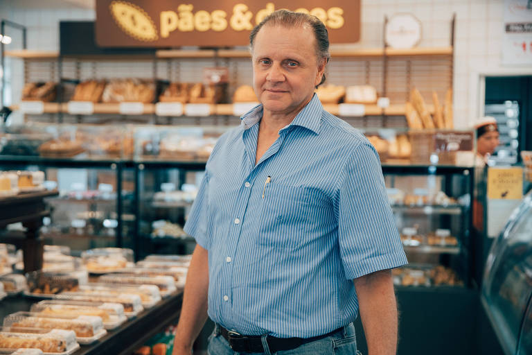 Homem de camisa azul ao lado de pães