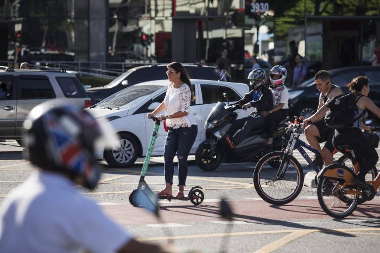 No primeiro plano, o capacete de um motociclista, umamoça sobre um patinete cruza a rua, seguida por ciclistas. Atra´s há carros e moto esperando o sinal abrir