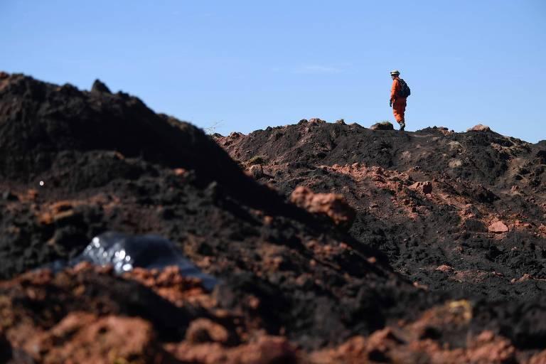 homem sobre escombros de lama