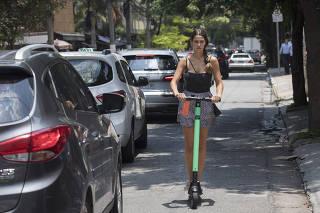 ***Especial Patinetes eletricos invadem bairro Itaim Bibi*** Mulher anda de patinete na rua Pedroso Alvarenga