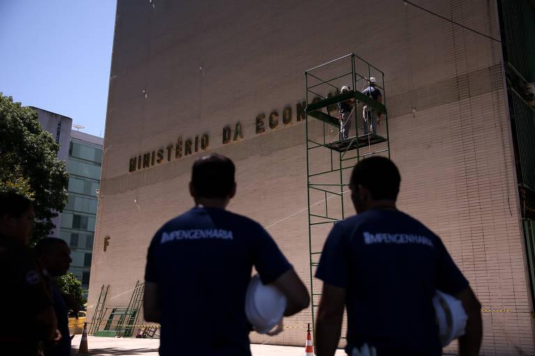 Funcionários colocam letreiro do Ministério da Economia, no prédio onde funcionava o Ministério do Trabalho, na Esplanada dos Ministérios