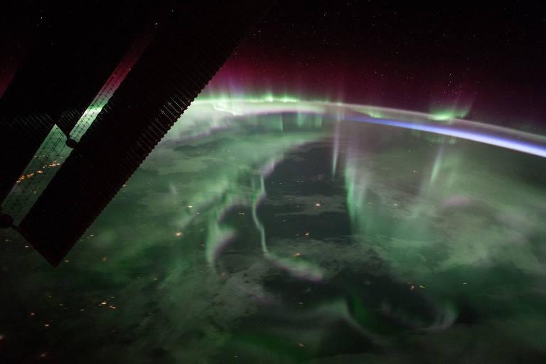 Aurora boreal sobre o Canadá, vista da Estação Espacial Internacional; imagem é causada pela partículas carregadas do Sol que interagem com o campo magnético da Terra