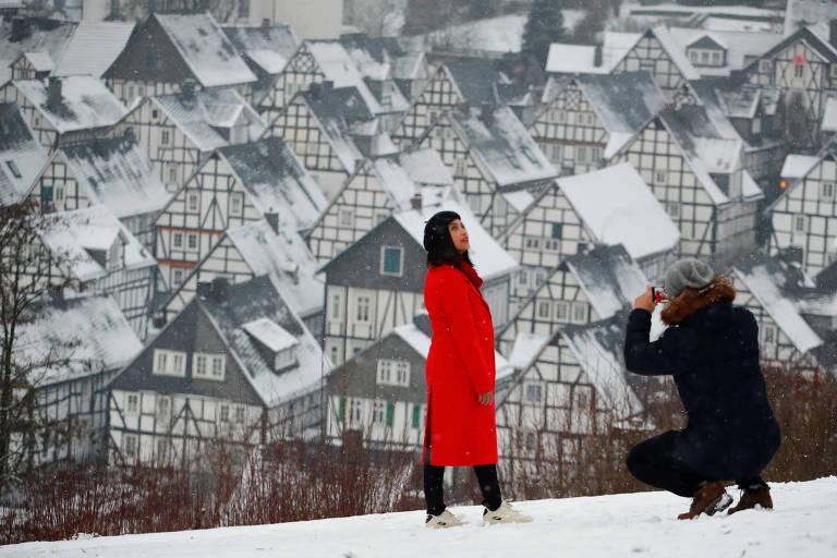 Mulher de casaco vermelho posa em cima de colina com vista de casas históricas cobertas de neve ao fundo