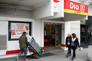 FILE PHOTO: People walk outside a DIA supermarket in central Madrid