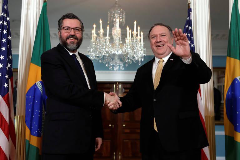O chanceler Ernesto Araújo e o secretário de Estado americano, Mike Pompeo, apertam as mãos e sorriem