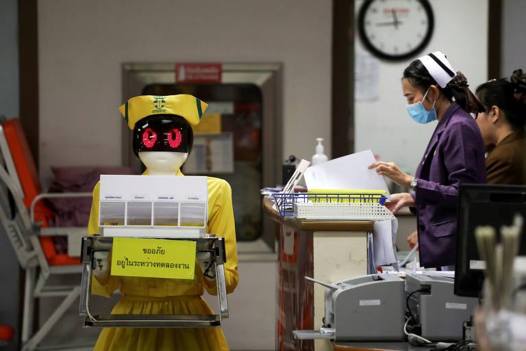 Robô vestido de enfermeira carrega documentos em hospital em Bangcoc, na Tailândia