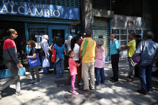 People wait in line outside of a currency exchange house in Caracas