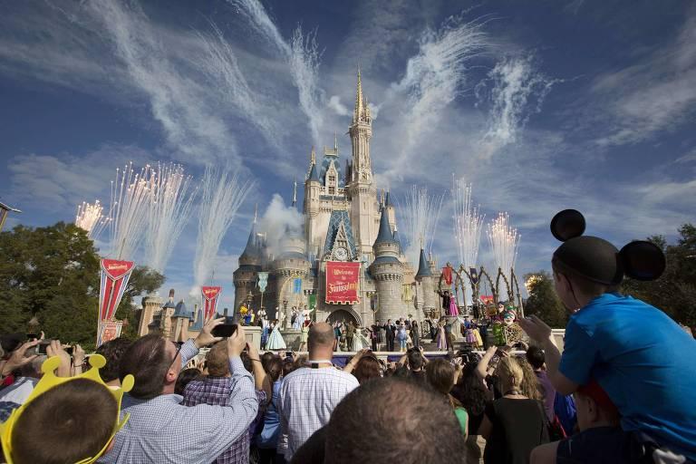 Pessoas em frente a castelo, com fogos saindo