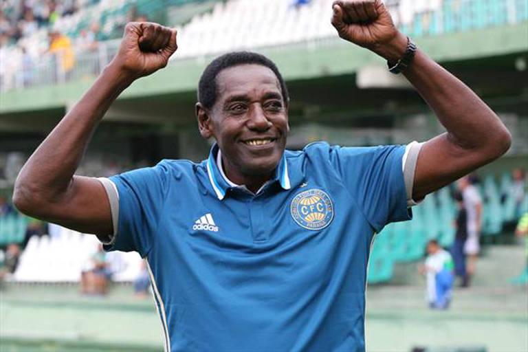 O ex-goleiro Jairo celebra com as mãos para cima. Ele veste uma camiseta azul do time de futebol do Coritiba