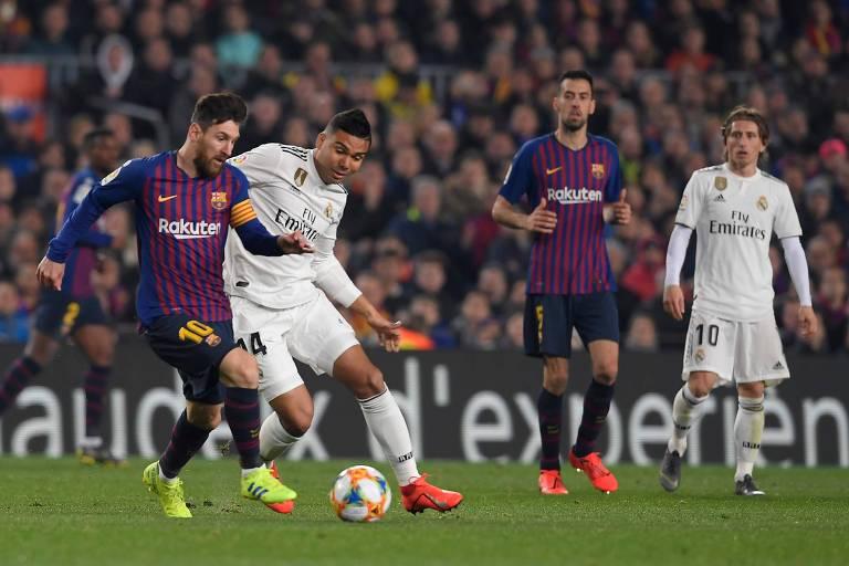 Messi e Casemiro disputam a bola em partida entre Barcelona e Real Madrid, times que dominam o Campeonato Espanhol