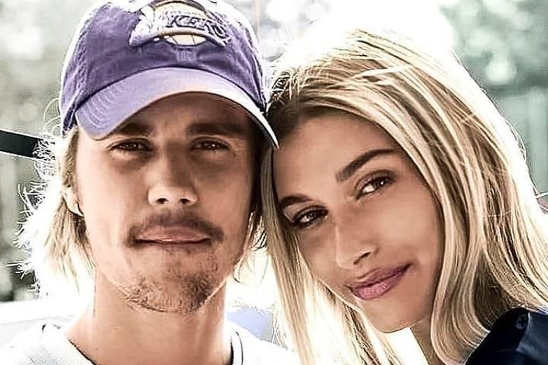 Justin Bieber de camiseta branca e boné abraçado a mulher Hailey Bieber, que usa casaco preto