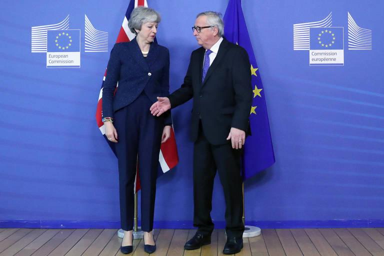 O presidente da Comissão Europeia, Jean-Claude Juncker (dir.), cumprimenta a primeira-ministra britânica, Theresa May, em Bruxelas nesta quinta (7)
