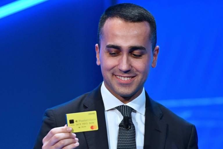 Homem de terno exibe um cartão de crédito