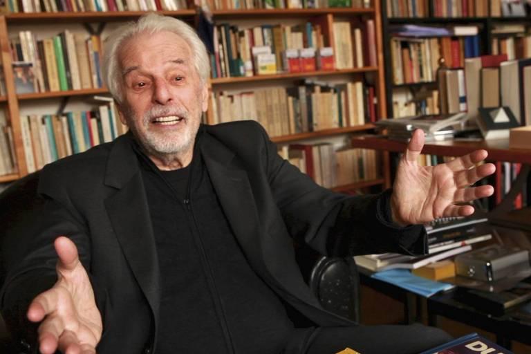 um homem de cabelos e barbas brancas em uma sala com muitos livros