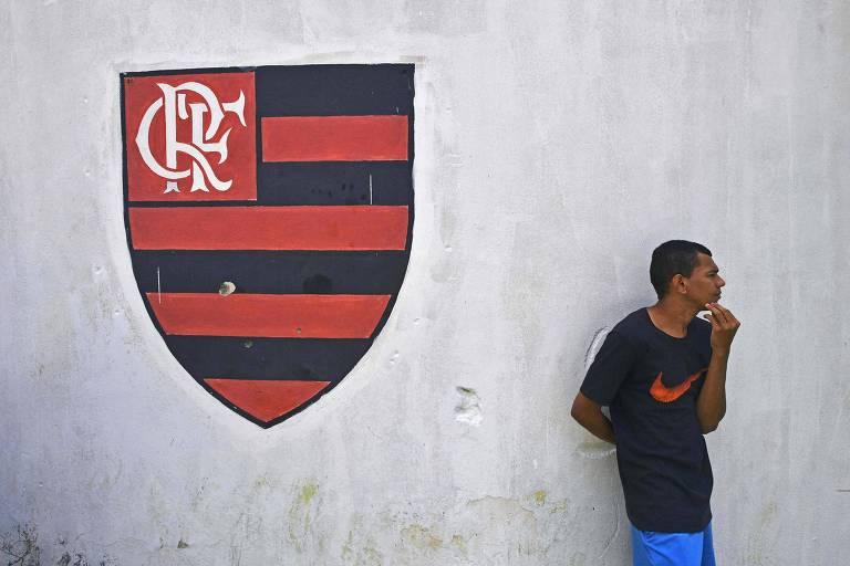 Homem ao lado do brasão do Flamengo do lado de fora do centro de treinamentos do Flamengo