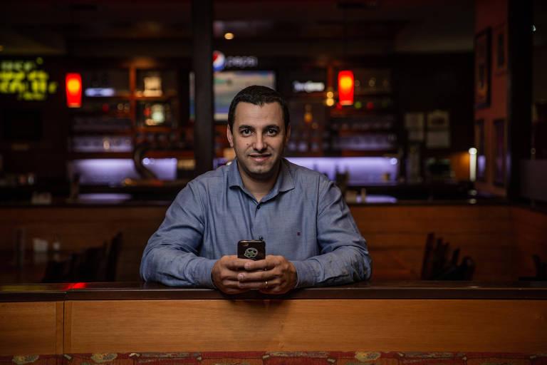 Homem com camisa azul segura aparelho celular na mão
