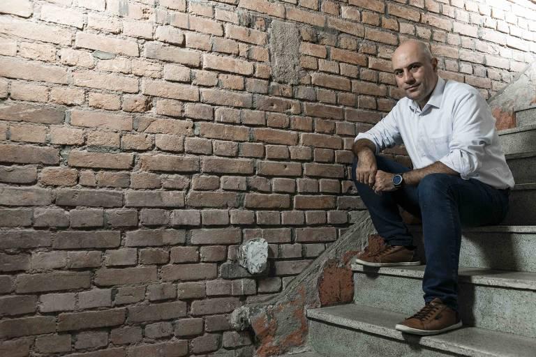 Homem careca de camisa branca sentando em escada, com parede de tijolinhos ao lado