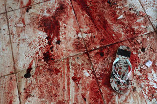 A sandal is seen on a blood-stained floor at a house where police officers confronted suspects during an operation against drug gangs at Fallet slum in Rio de Janeiro