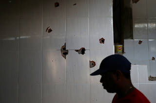 A man is seen against the wall with bullet holes at a house where police officers confronted suspects during an operation against drug gangs at Fallet slum in Rio de Janeiro