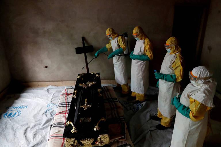 Agentes de saúde durante funeral de pessoa suspeita de ter morrido por ebola na República Democrática do Congo