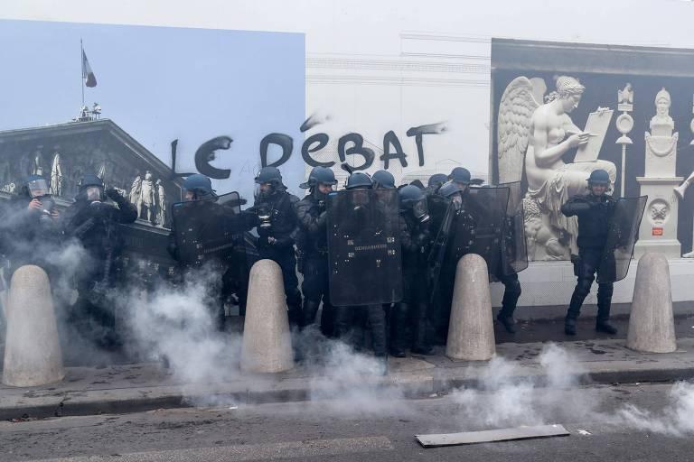 Os policiais franceses ficam em meio a fumaça de gás lacrimogêneo do lado de fora da Assembleia Nacional em Paris, durante o 13º protesto dos 'coletes amarelos' em Paris