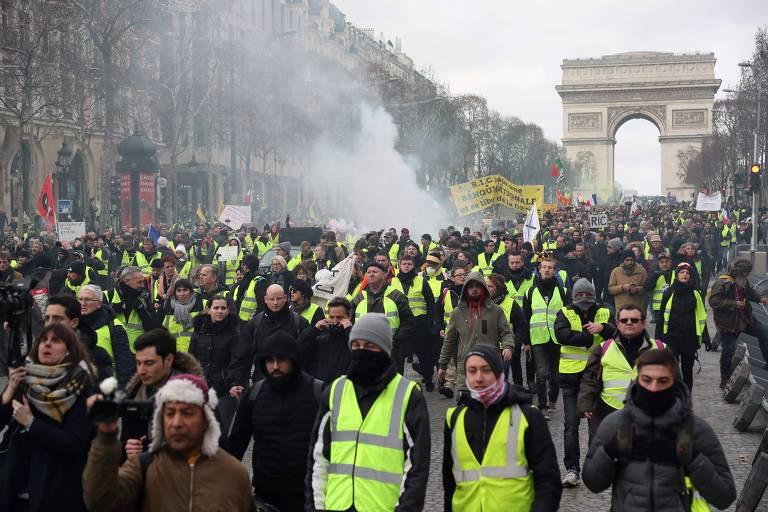 Manifestantes com coletes amarelos caminham perto do Arco do Triunfo durante o 13º sábado de protestos na França