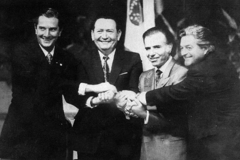 Quatro homens se dão as mãos com bandeira ao fundo