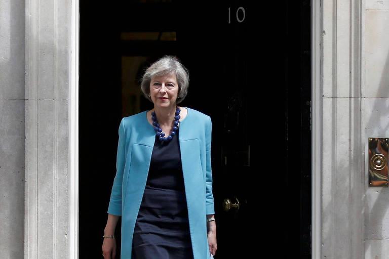 Mulher de roupa azul e cabelo grisalho deixa residência