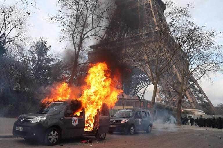 """Carro da polícia pega fogo, diante da Torre Eiffel, após ser alvo de ataque durante 0 13º sábado de protestos dos """"coletes amarelos"""" em Paris"""