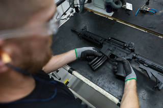 An employee from gun manufacturer Taurus Armas SA works at the company's assembly line in Sao Leopoldo